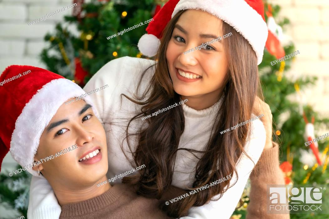 Stock Photo: Young asian adult teenager couple hugging and celebrateing christmas holiday together in living room with christmas tree ornament decoration.