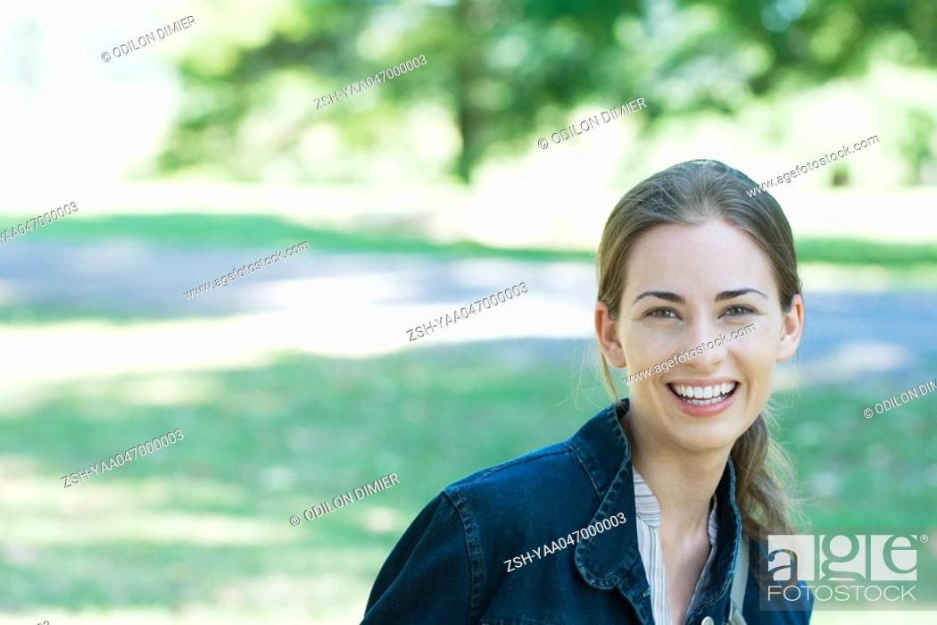 Stock Photo: Young woman wearing jacket, outdoors, smiling at camera, focus on foreground.
