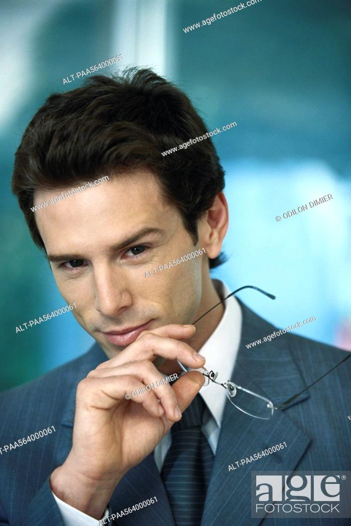 Stock Photo: Businessman with holding glasses in hand, portrait.