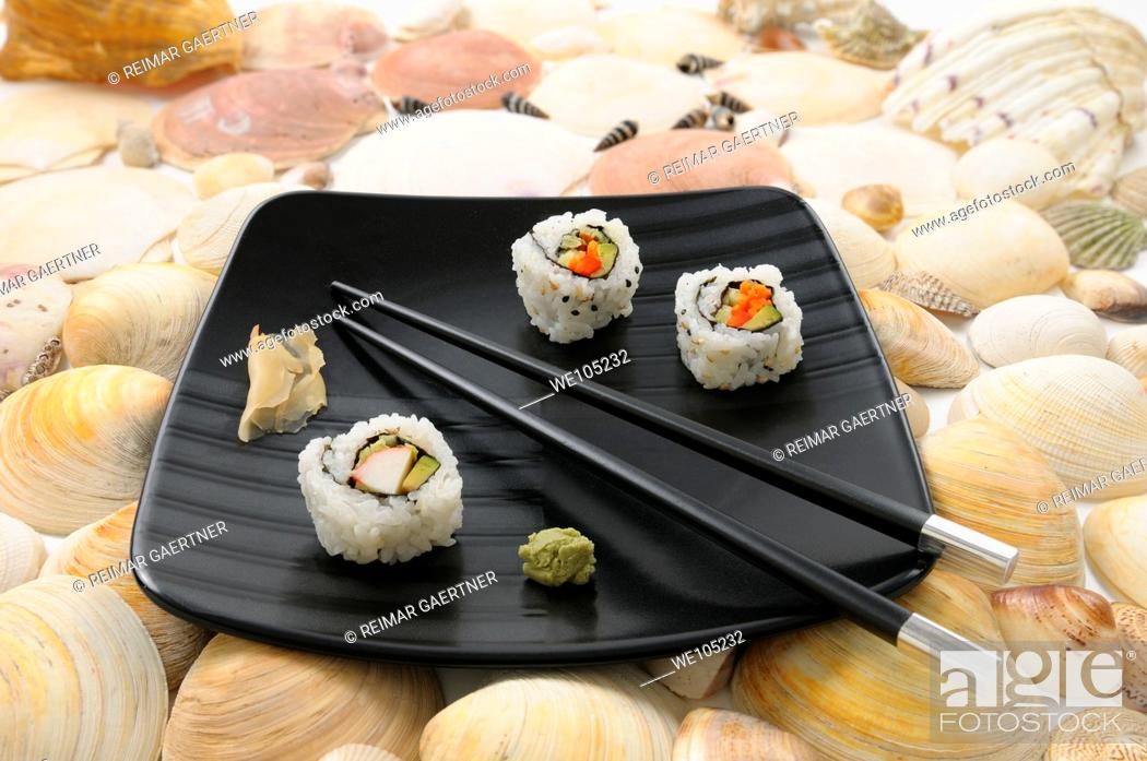 Stock Photo: Crab Uramaki sushi and chopsticks on a black plate surrounded by sea shells.