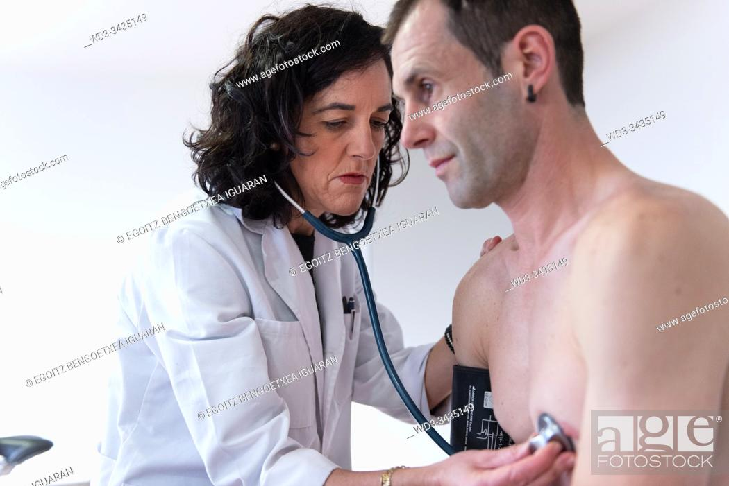 Stock Photo: A female doctor checking the heart health of a man with a stethoscope.