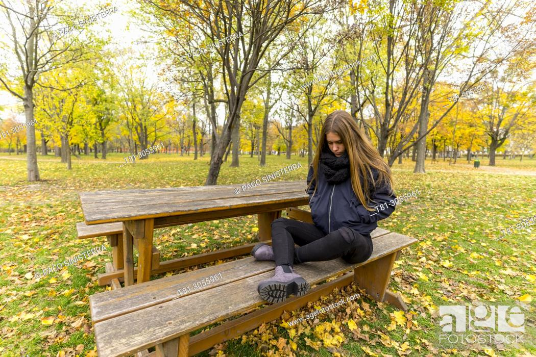 Imagen: Thoughtful girl sitting along on park bench in the Prater, Vienna, Austria.
