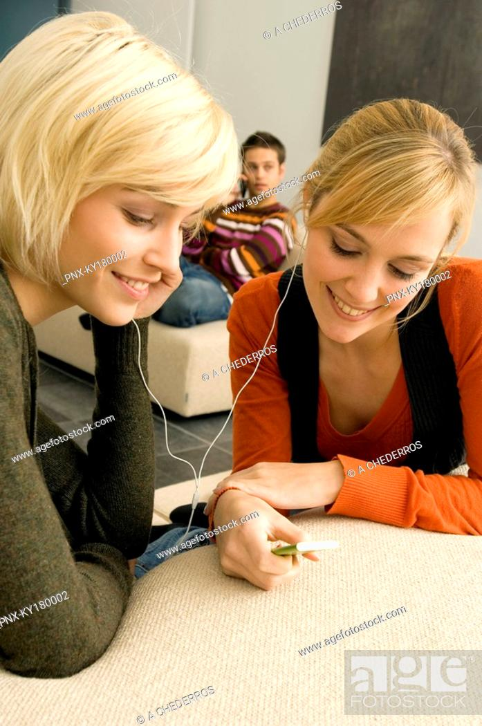 Stock Photo: Two young women listening to an MP3 player and smiling.
