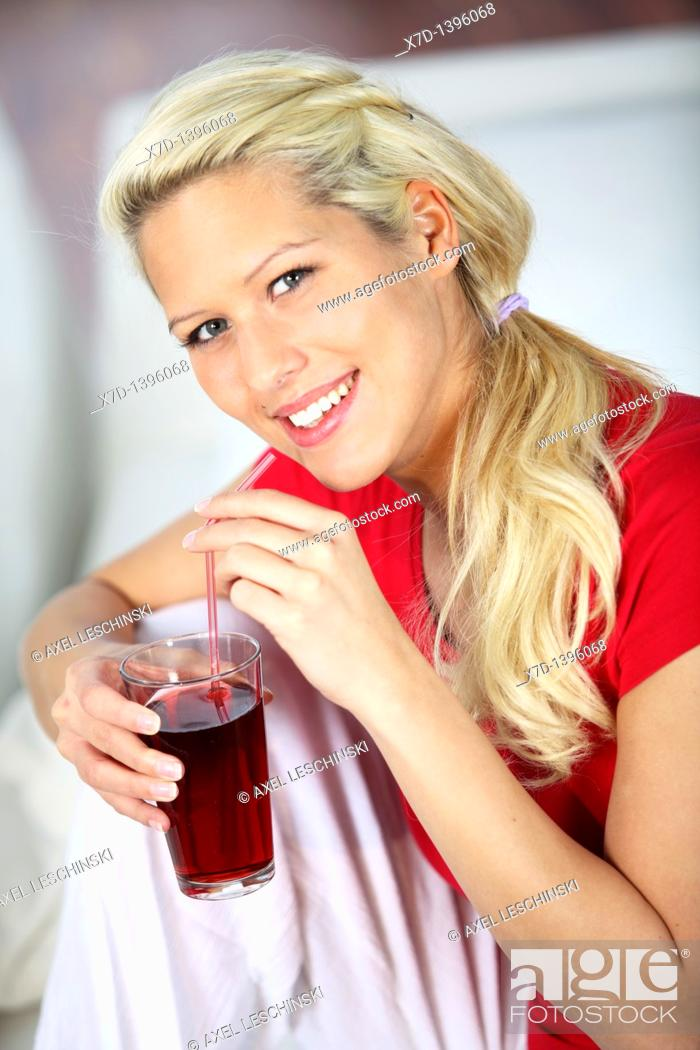 Stock Photo: blond woman relaxing on sofa drinking red fruit juice.