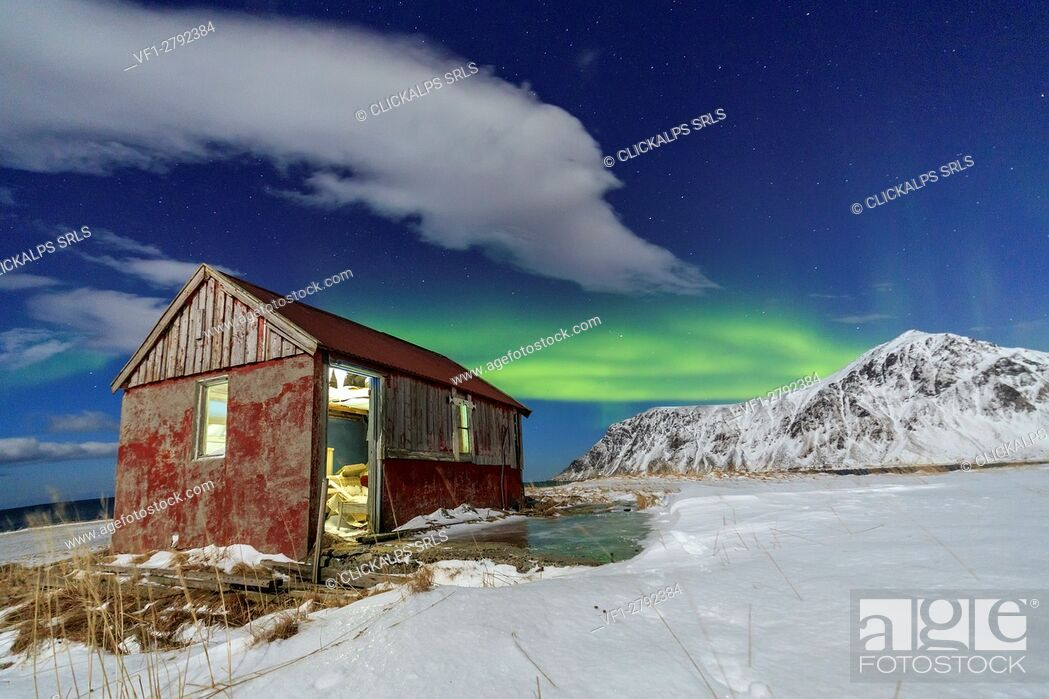 Stock Photo: Northern Lights over an abandoned log cabin surrounded by snow and ice. Flakstad. Lofoten Islands Northern Norway Europe.