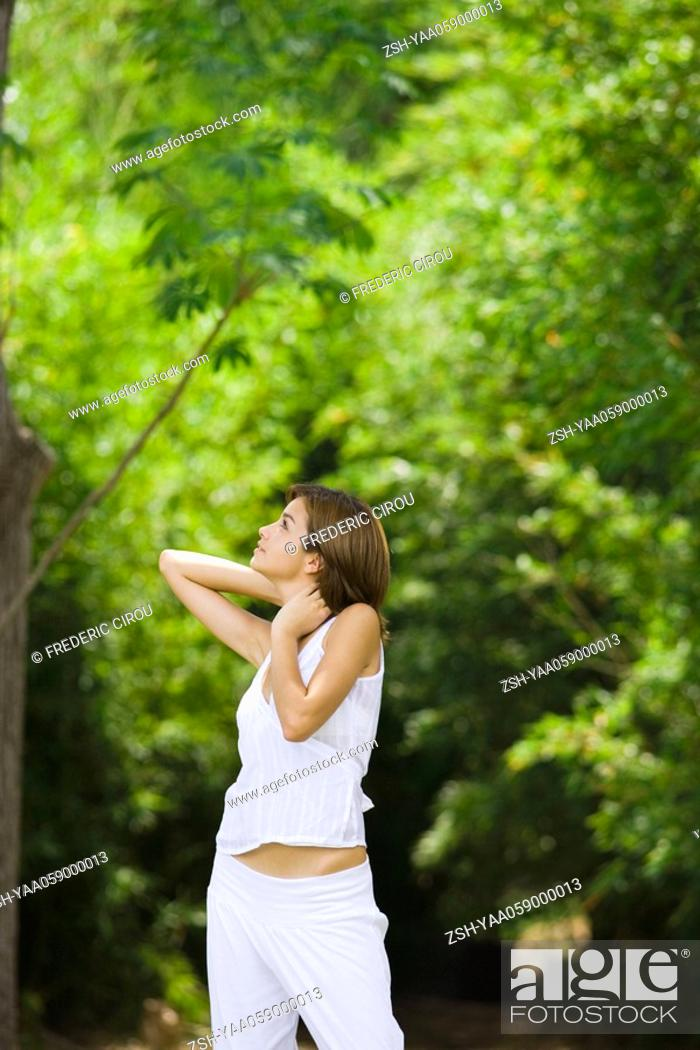 Stock Photo: Young woman standing with hands behind neck, looking up.