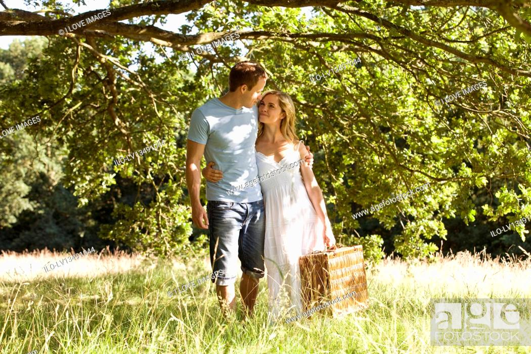 Stock Photo: A young couple carrying a picnic basket.