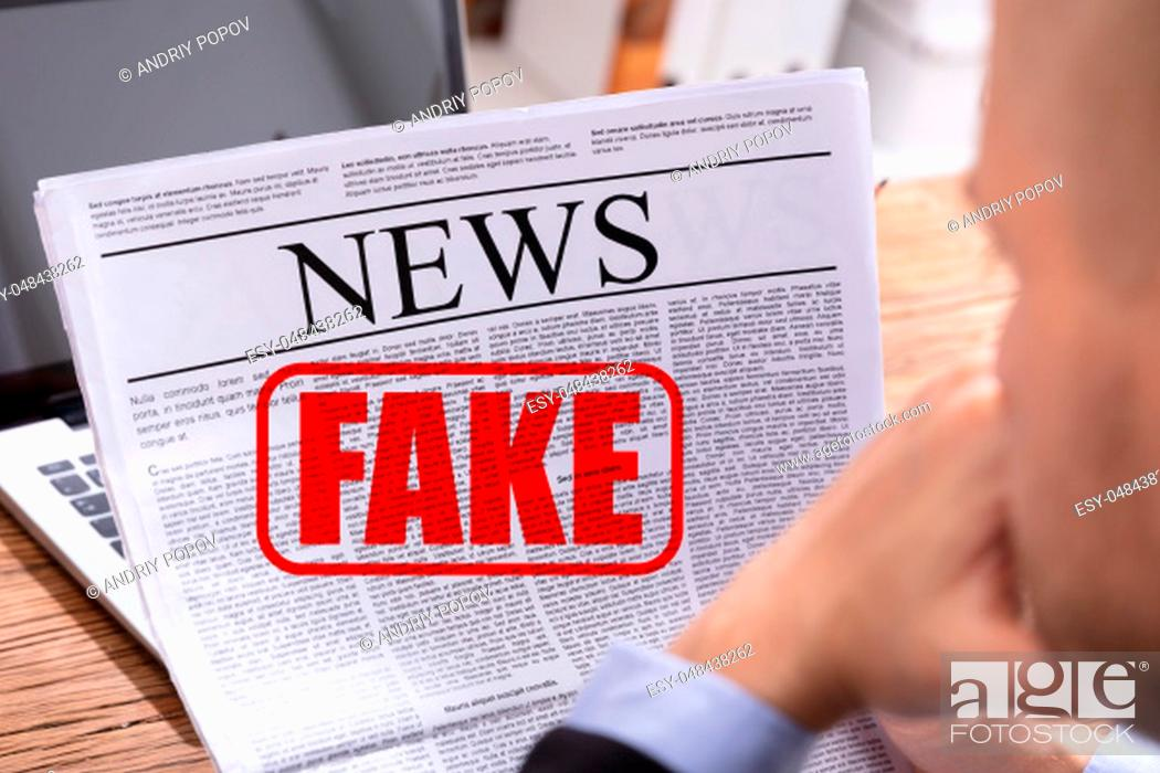 Stock Photo: Man Reading Fake News In Newspaper Over Desk.
