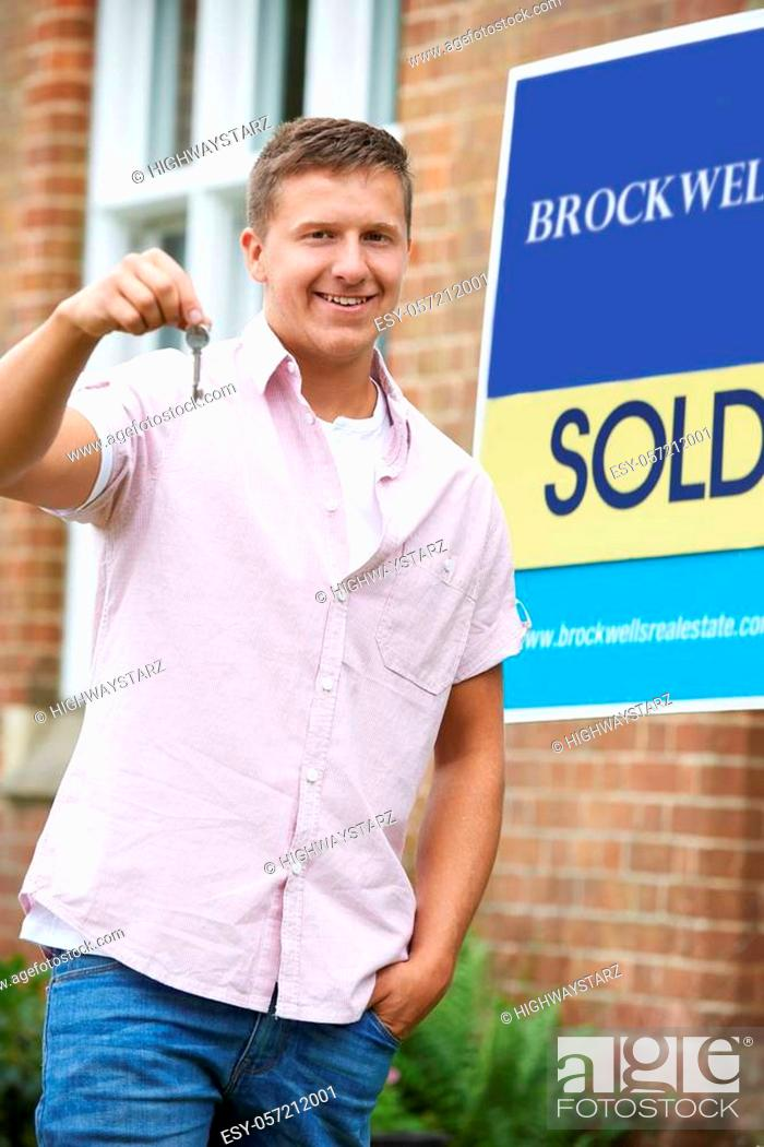 Stock Photo: Portrait Of Excited Man Standing Outside New Home With Sold Sign Holding Keys.