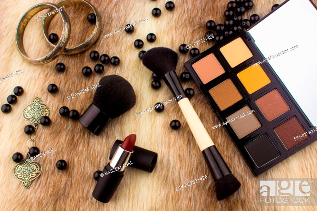 Imagen: Makeup tools on Fur background / featuring eyeshadow palette, lipstick, makeup brushes on a fury background.