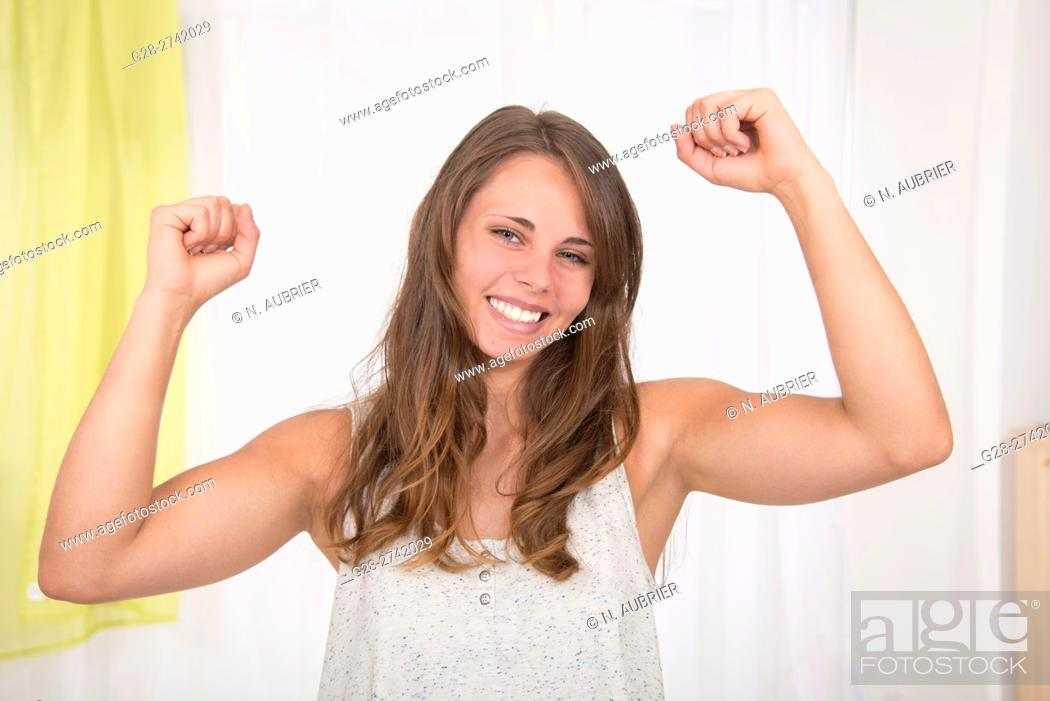 Stock Photo: Young woman lifting hers arms to express her happiness.