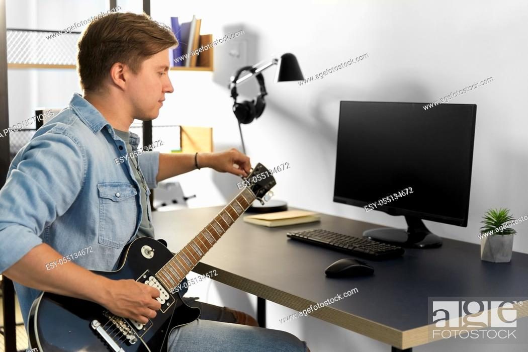 Imagen: young man with computer playing guitar at home.