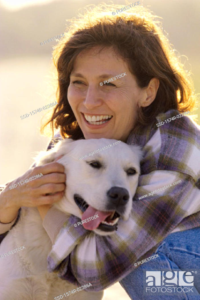 Stock Photo: Mid adult woman hugging her dog.