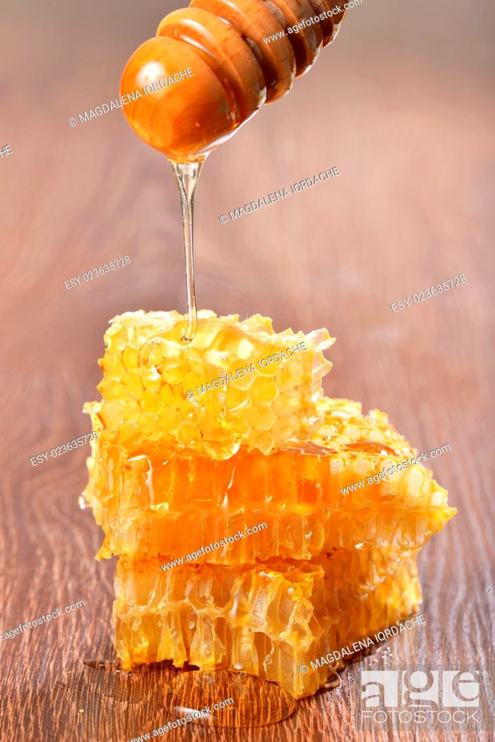 Stock Photo: Honey dripping on honeycombs on wooden background.