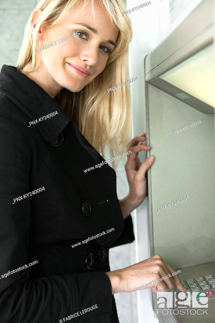Stock Photo: Woman entering pin number in an ATM.