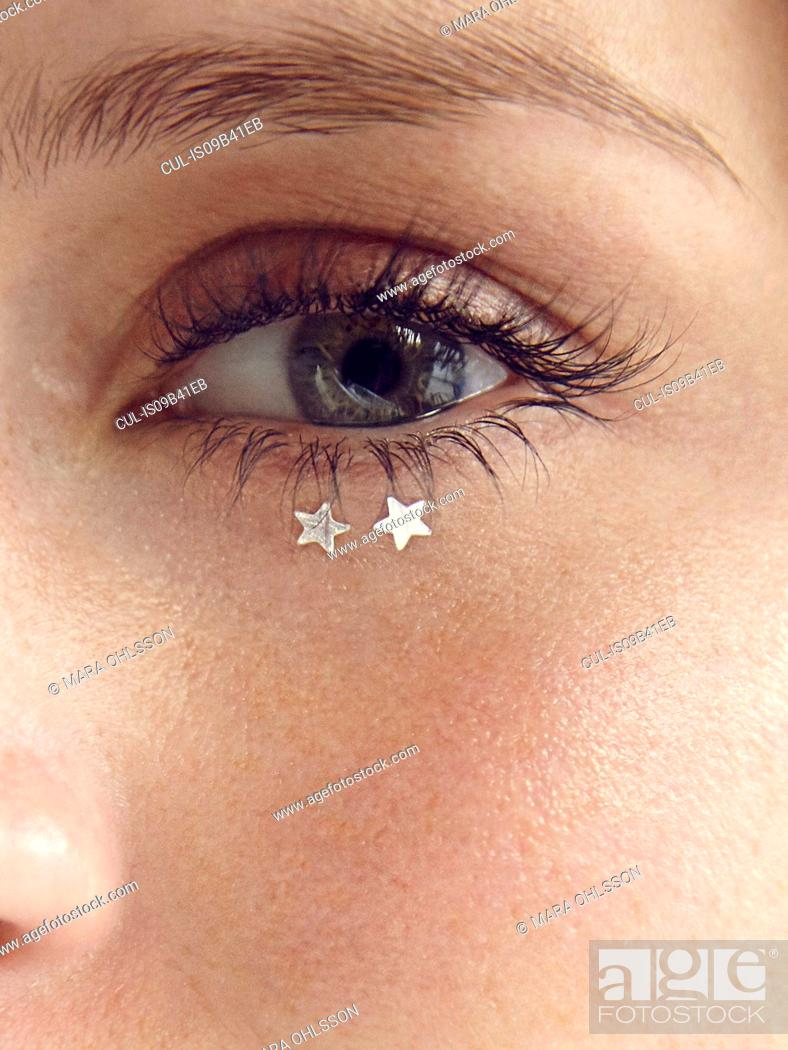 Stock Photo: Close up of glitter stars under young woman's eye.
