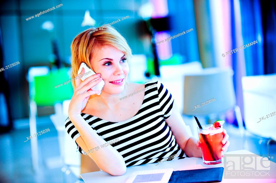 Stock Photo: young, pretty woman reading e-book, smartphone, cocktail.