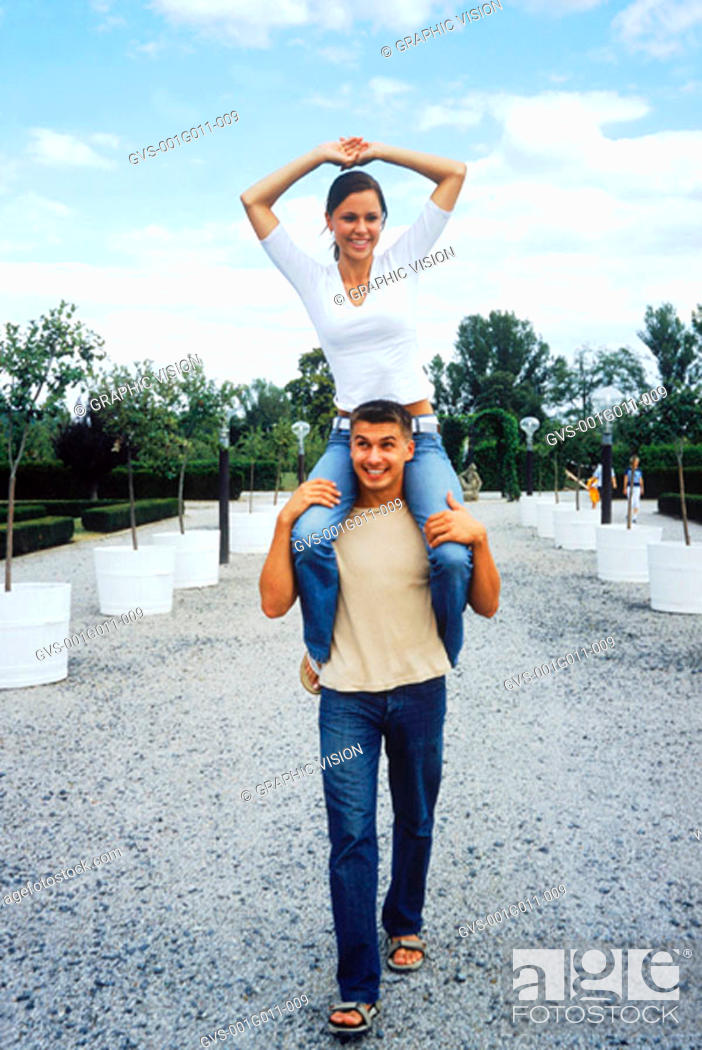 Stock Photo: Young woman riding on young mans shoulders.