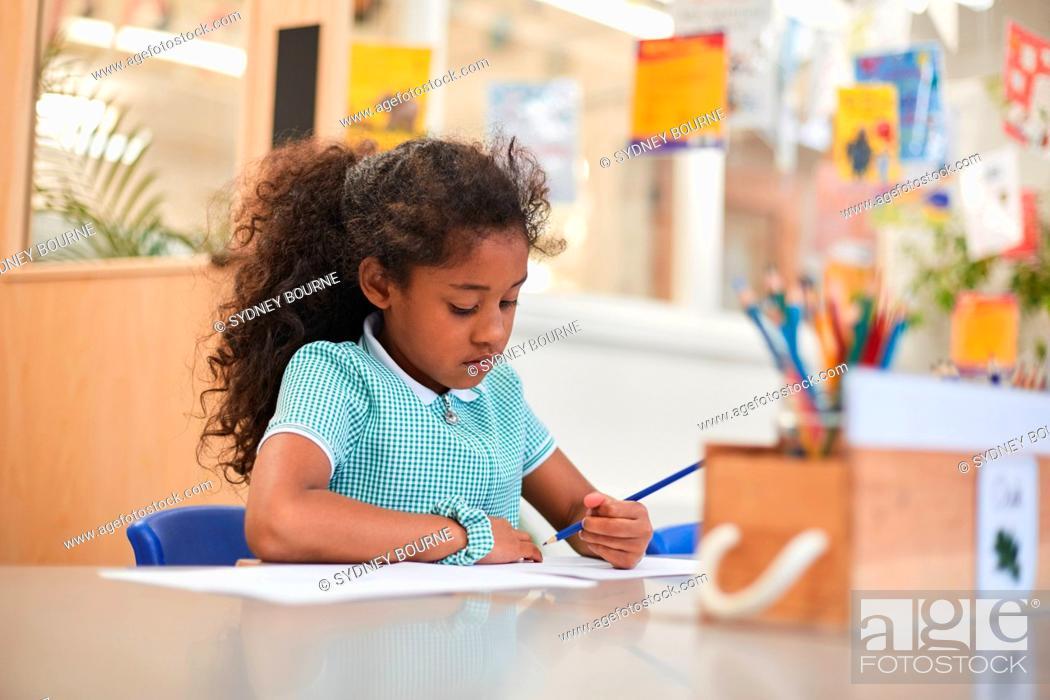 Stock Photo: Schoolgirl writing at classroom desk in primary school.