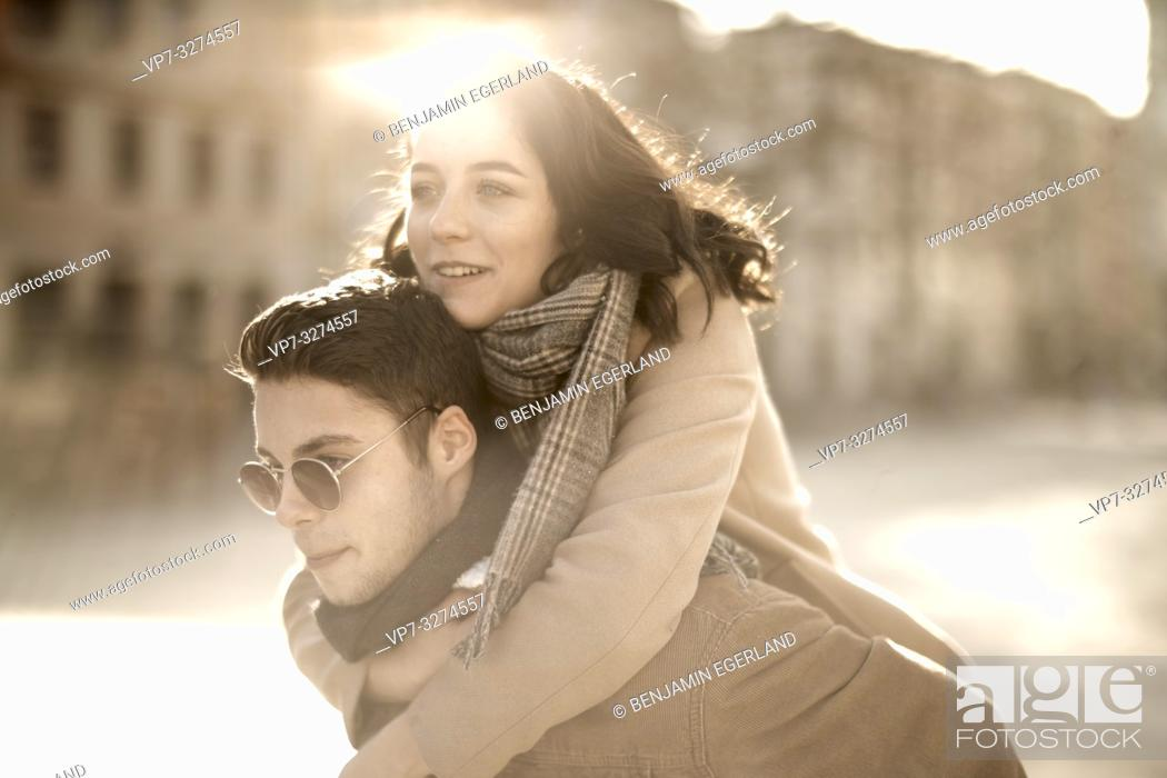 Stock Photo: teenage woman embracing boyfriend from behind outdoors in sunlight in city, in Cottbus, Brandenburg, Germany.