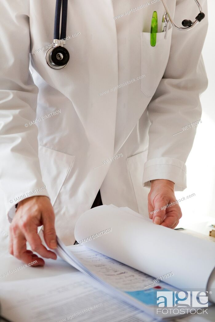 Stock Photo: Doctor reading patients file.
