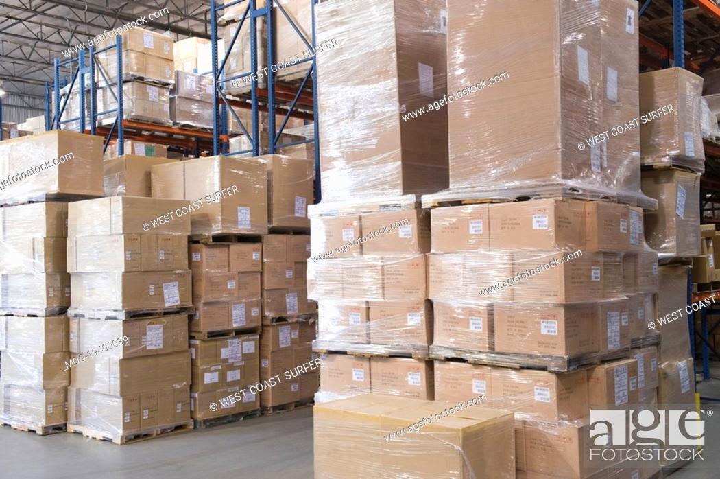 Stock Photo: Cardboard boxes stacked in distribution warehouse.