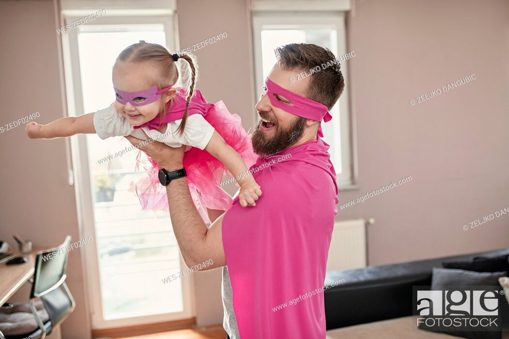 Stock Photo: Father and daughter playing superhero and superwoman, pretending to fly.