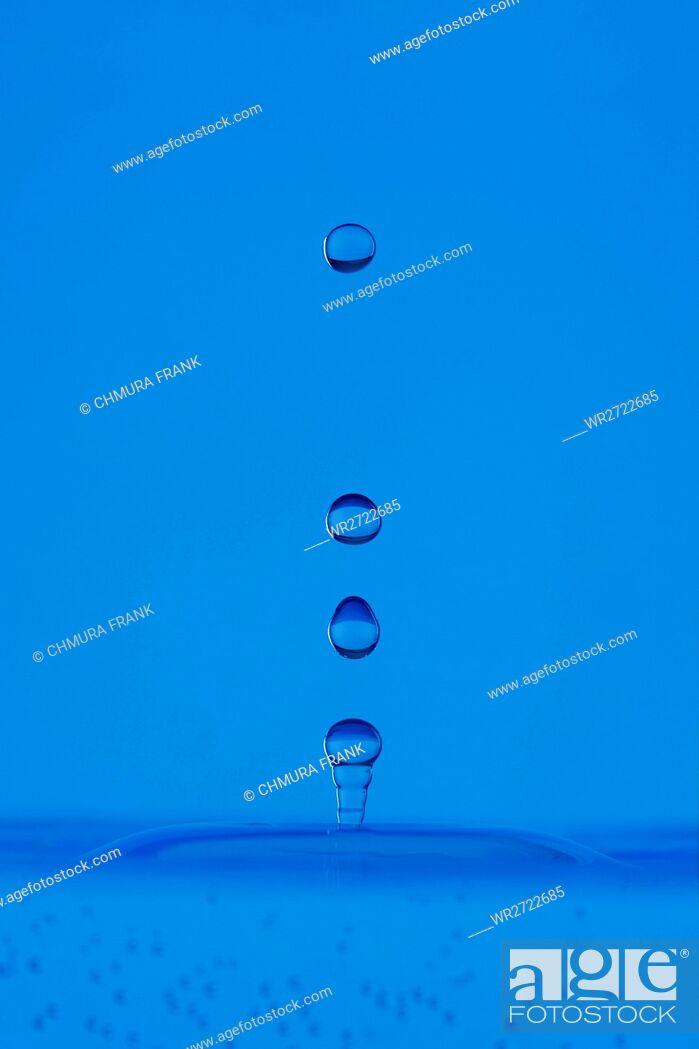 Stock Photo: blue droplet hitting the water surface splashing it up.