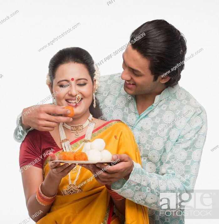 Imagen: Man feeding prasad to a woman on Gudi Padwa festival.