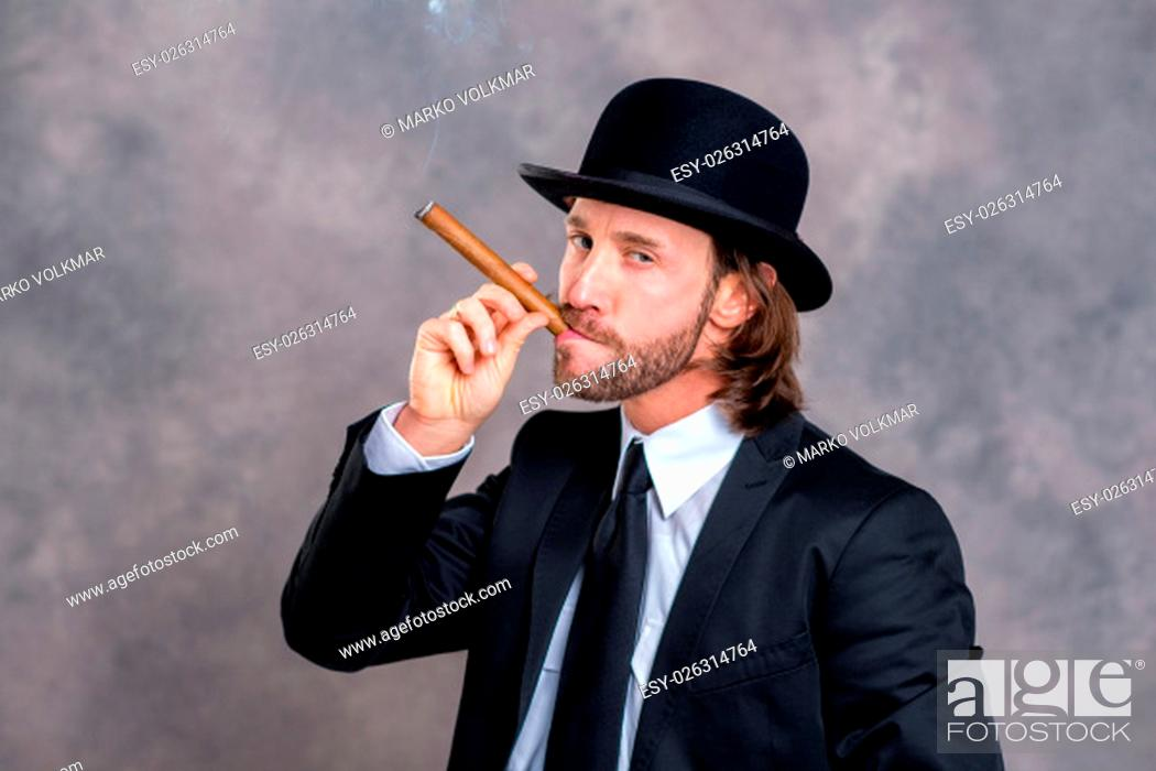 Stock Photo: young businessman with bowler hat in black suit smoking big cigar.