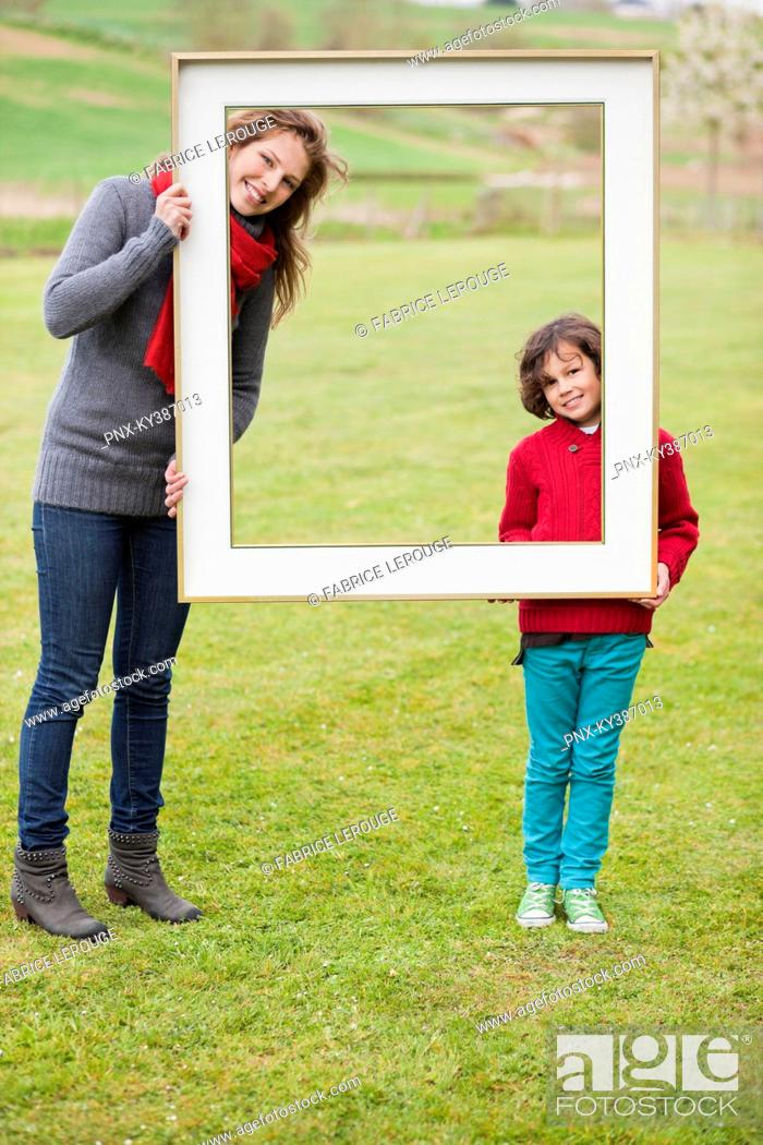 Stock Photo: Woman and her son standing with a frame in a park.