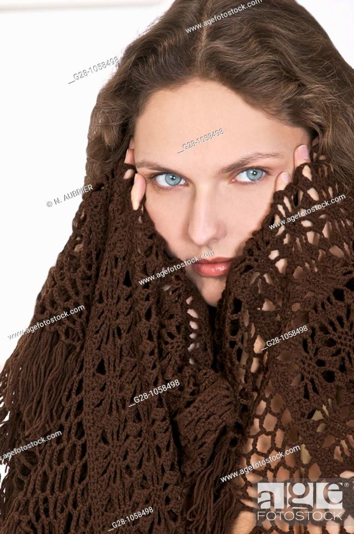 Stock Photo: young woman in a brown shawl,holding her temples because of  a headache.
