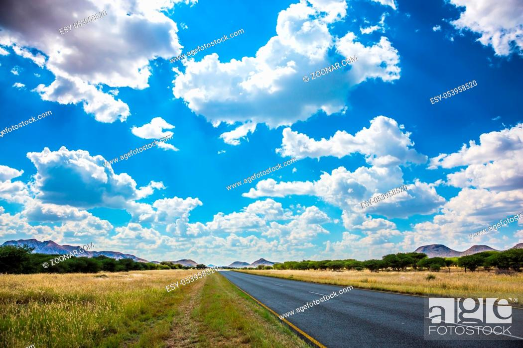 Stock Photo: Along the road low trees and yellowed grass. Fluffy clouds over the savannah. The good asphalt highway in Namibia.