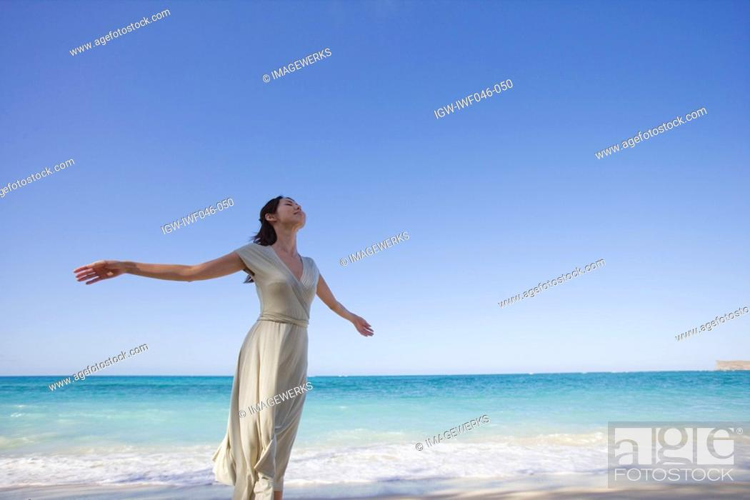 Stock Photo: A young woman standing on beach.