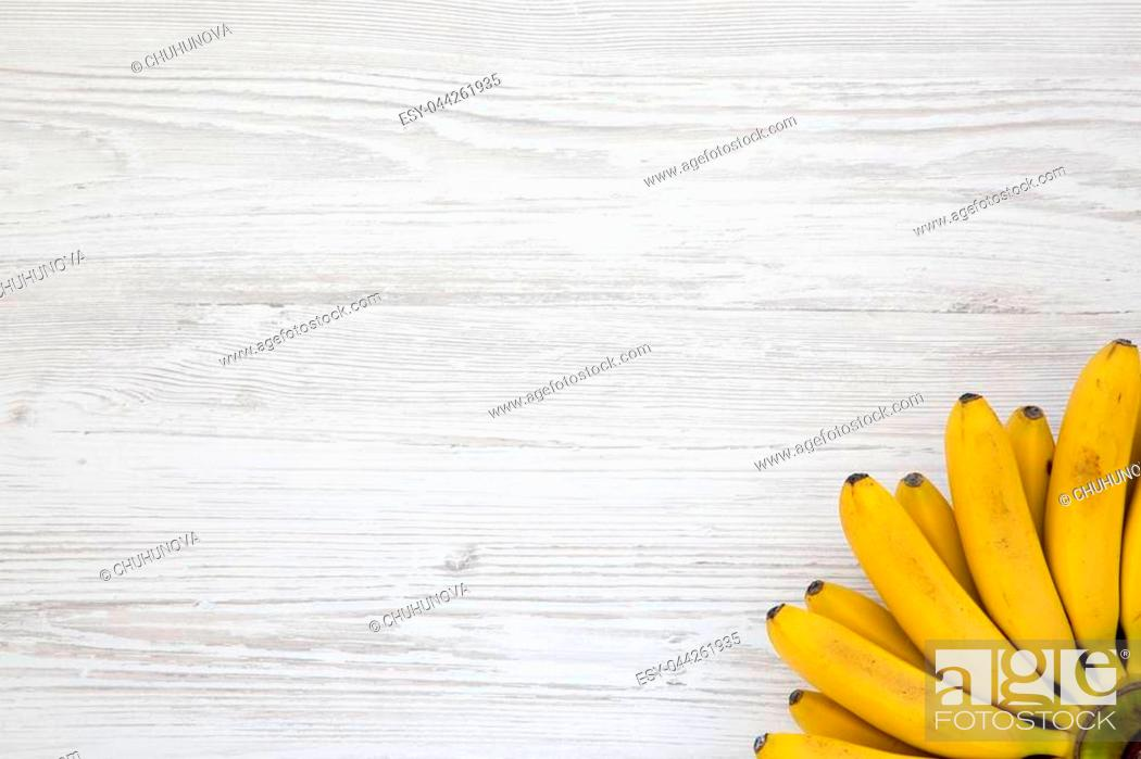 Stock Photo: Bunch of baby banana on white wooden background, top view. Copy space.