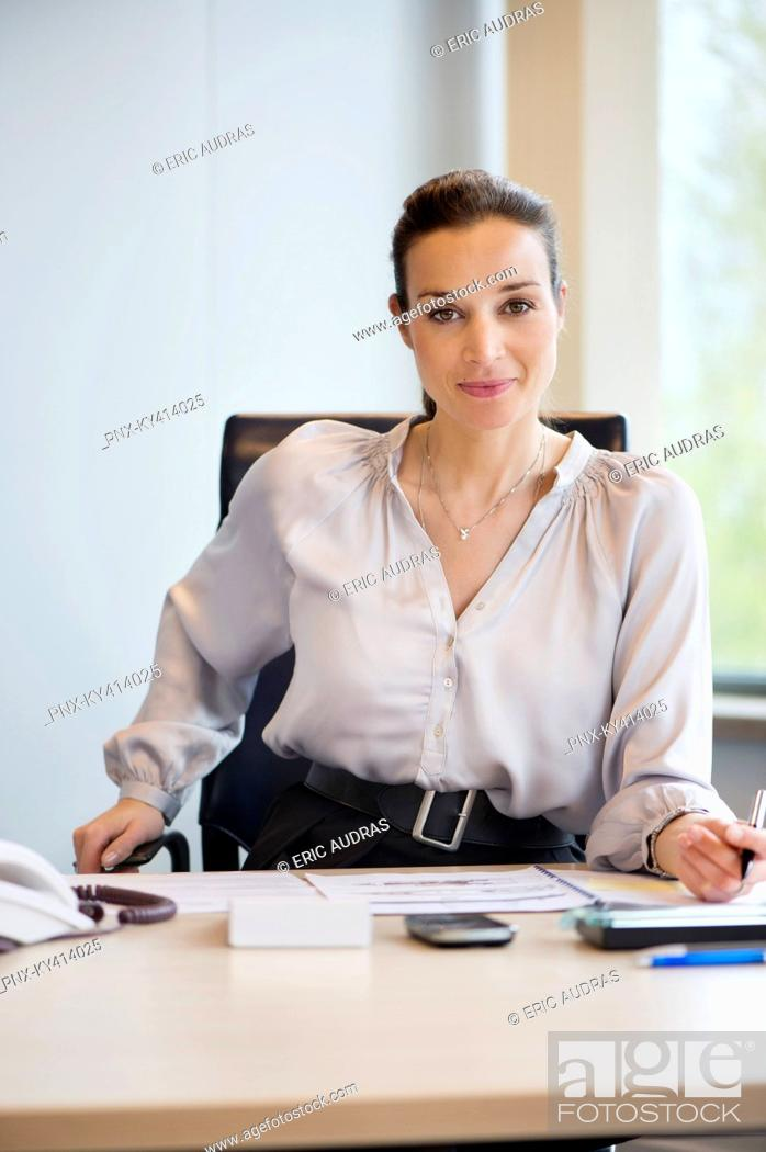 Stock Photo: Portrait of a businesswoman working in an office.