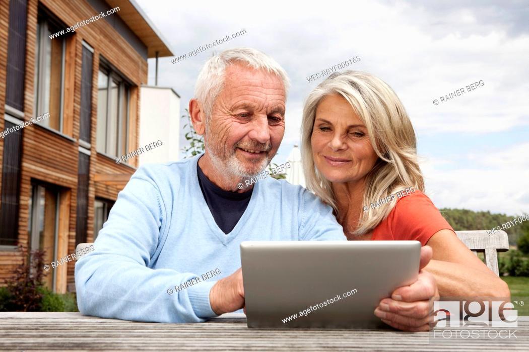Stock Photo: Germany, Bavaria, Nuremberg, Senior couple using digital tablet.