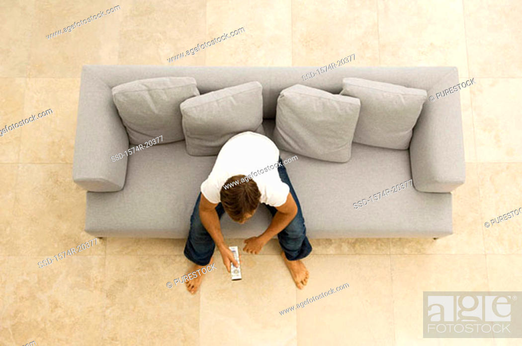 Stock Photo: High angle view of a young man sitting on a couch with a remote control.