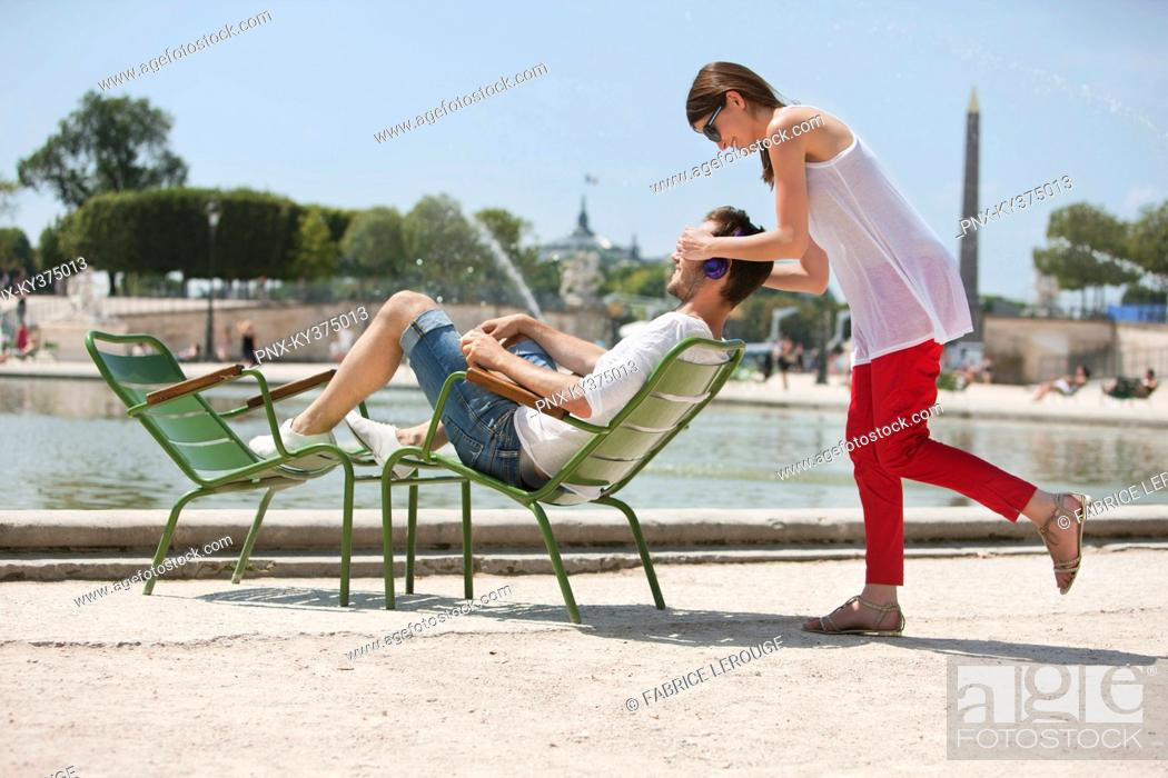 Stock Photo: Woman covering eyes of a man with her hands, Bassin octogonal, Jardin des Tuileries, Paris, Ile-de-France, France.