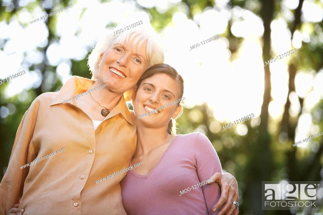 Stock Photo: Grandmother and Granddaughter in back yard portrait low angle view.