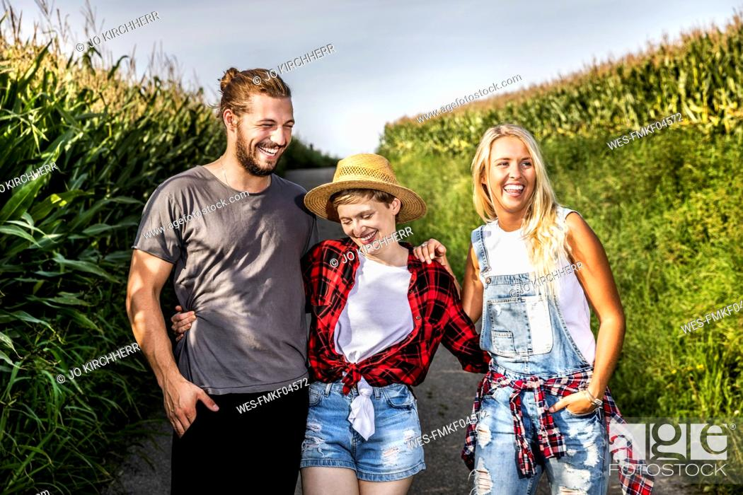 Stock Photo: Happy friends on country lane at a cornfield.
