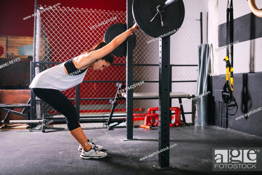 Stock Photo: Athletic brunette young woman doing some weightlifting exercises.