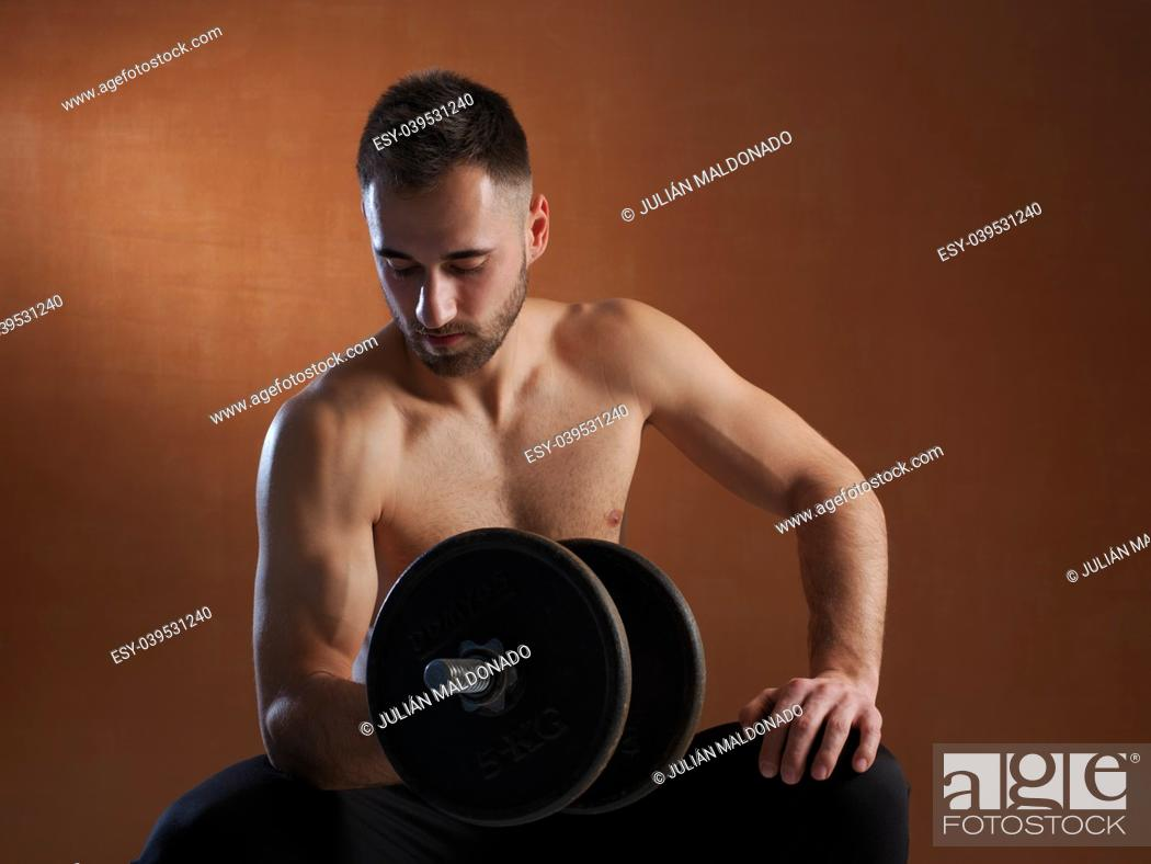 Stock Photo: Young man training with weight lifting.