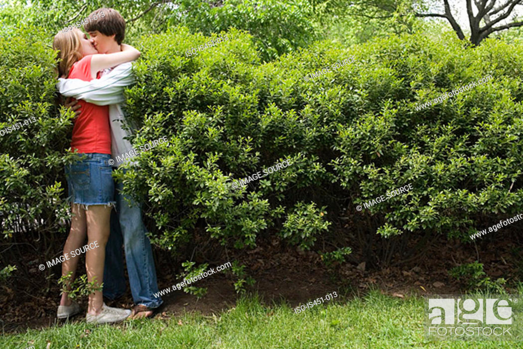 Stock Photo: Teenage couple kissing in bush.