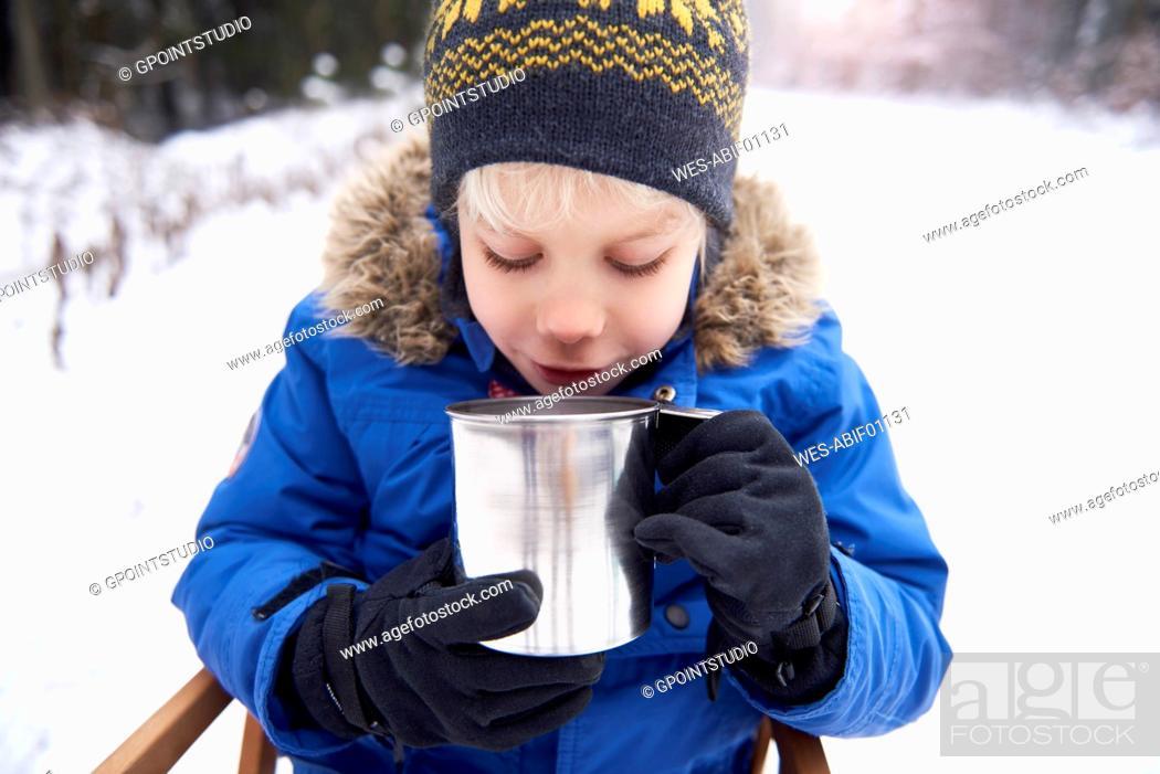 Stock Photo: Little boy sitting on sledge drinking tea.
