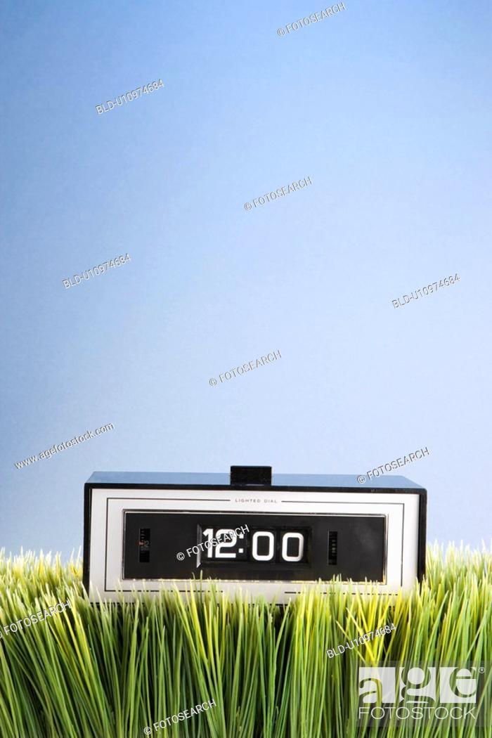 Stock Photo: Studio shot of retro alarm clock placed in grass.