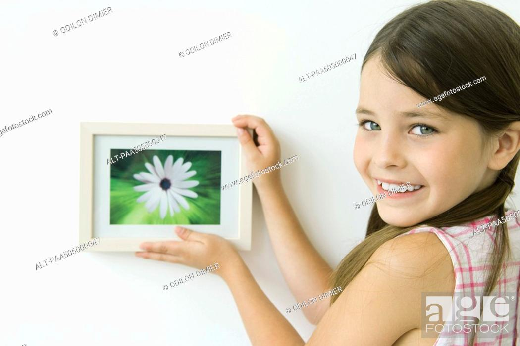 Stock Photo: Little girl holding framed picture against wall, smiling over shoulder at camera.