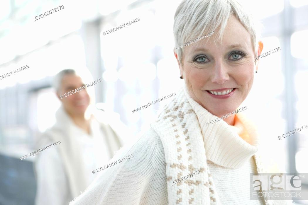 Stock Photo: Happy mature woman at airport with man behind.