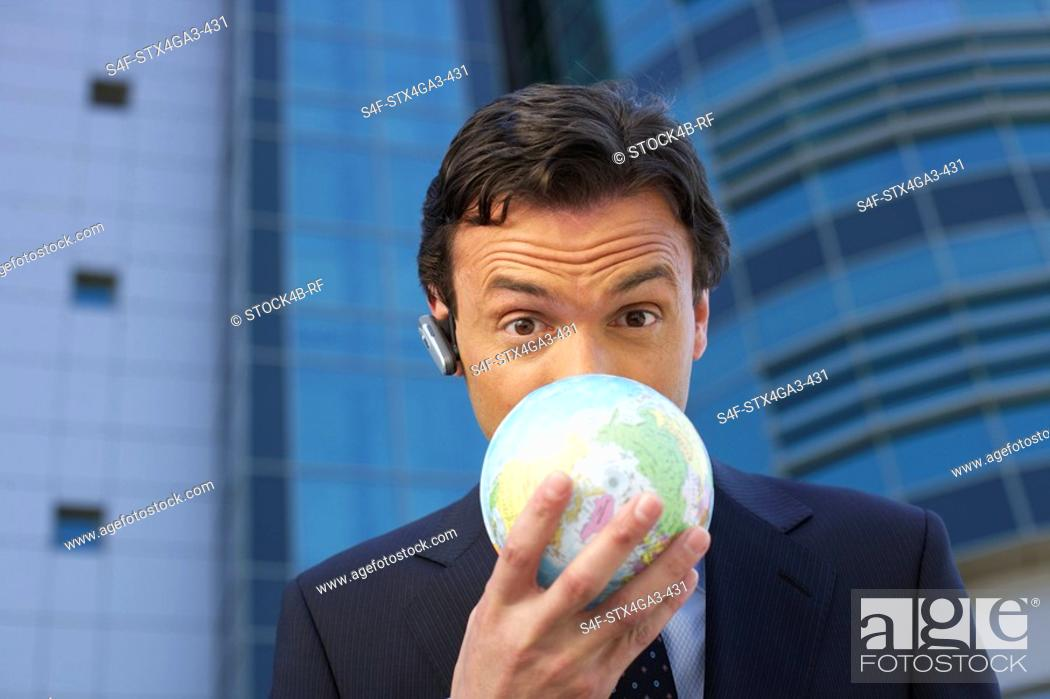 Stock Photo: Businessman covering his face with an earth ball.