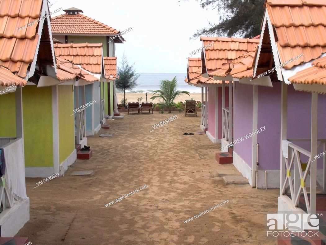 Stock Photo: Attractive pastel colored tiled bungalows at quiet Patnem Beach south Goa India.